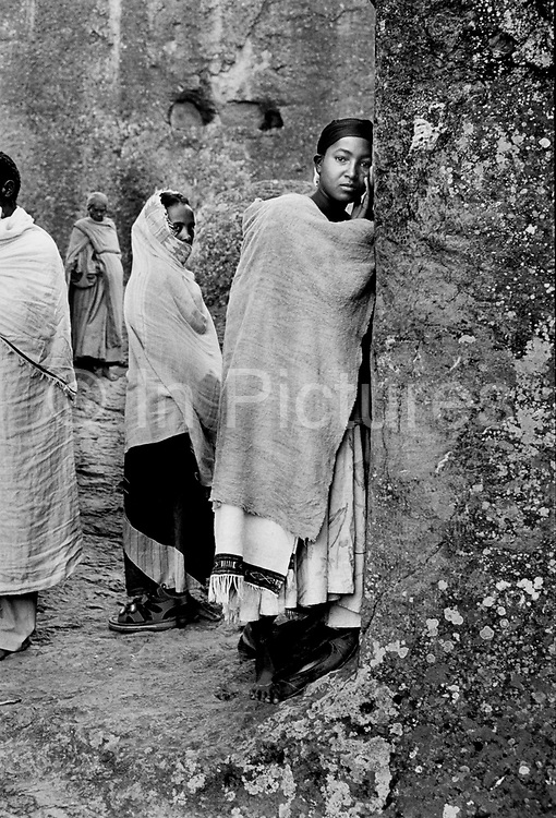 Ethiopian Orthodox pilgrims at Lalibela, Ethiopia.As dawn breaks, nuns pray outside the tiny chapel of Bet danaghel which was constructed in honour of fifty Christian maiden nuns murdered in the fourth century by the Roman Julian Apostate. Lalibela in northern Ethiopia is famous for it's monolithic roack hewn churches and is one Ethiopia's holiest cities and a centre of pilgrimage for much of the country.
