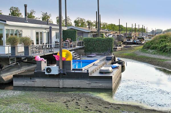 Nederland, Beneden Leeuwen, 4-8-2018 In een leeggelopen, drooggevallen, strang van de Waal liggen woonschepen op het droge, op de bodem .Door de droogte in heel europa is het peil van de rivier zo laag dat de inham droog staat . Foto: Flip Franssen
