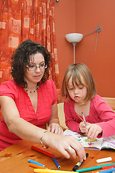 Mother with daughter doing colouring.