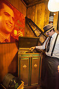 Mozo (waiter) plays Gardel 78 rpm record while wearing Carlos Gardel tie  (portrait of famous singer/tango dancer  from 1920s above), Ramos Generales cafe, Ushuaia, Argentina.