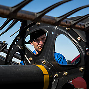 Alan Stoner, 21, looks on as a combine header is repaired during wheat harvesting. Malfunctions and repairs are an accepted disruption of harvest. Crowell, Texas, May 2017.