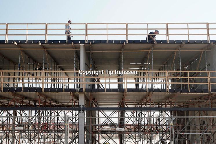 Nederland, Maastricht, 9-4-2020  Bouwvakkers werken mat afstand tot elkaar op deze bouwplaats bij het vliegveld zuid-limburg . Er komt een nieuw hotel .Foto: Flip Franssen