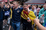 Scotland football supporters gather in the rain near Londons Leicester Square before tonights match between England and Scotland at Wembley, during the European Championships postponed for a year because of the Covid pandemic, on 18th June 2021, in London, England. The two nations have traditionally been fierce sporting rivals and this is the first time that Scotland has qualified for the Euros for 23 years.