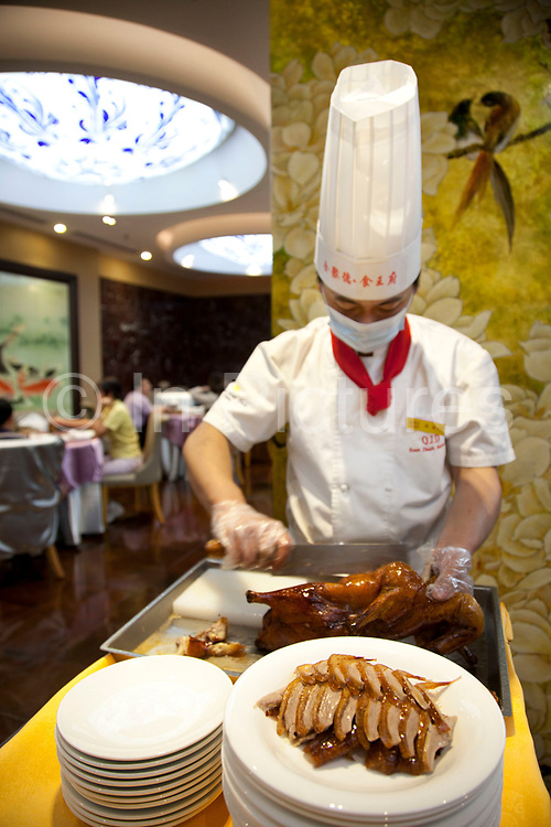 Chef carves a roast duck in the traditional manner in the main dining room, slicing the breast meat into thin slices, each with a small pieve of the savoured fat. Quanjude roast duck restaurant in Wangfujing, Beijing. This is a Chinese restaurant known for its trademark Peking Roast Duck and is known for being the best roast duck restaurant in China. Quanjude was established in 1864 during the Qing Dynasty under the reign of the Tongzhi Emperor. Although Peking Duck can trace its history many centuries back, Quanjude's heritage of roast duck preparation - using open ovens and non-smoky hardwood fuel such as Chinese date, peach, or pear to add a subtle fruity flavor with a golden crisp to the skin, was originally reserved for the imperial families.