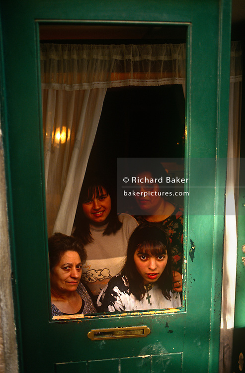 Portrait of a family looking out from street doorway in Lisbon's Bica district of the Portuguese capital. The family members huddle for this portrait, half in sunlight and others lit by the light from a lightbulb that lights the dark room behind. A grandmother, a mother and young girls look out from their home to the street outside. Lisbon's Bica district is a steep gradient area of narrow streets more peaceful and atmospheric than other busier locations where cars and trams make wider roads noisier. Flights of steps dissect the quarter which remains largely unspoilt.