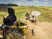 07 NOVEMBER 2014 - SITTWE, RAKHINE, MYANMAR: A Rohingya woman on a rickshaw taxi passes a blind beggar on train tracks in an IDP camp for Rohingya Muslims near Sittwe. After sectarian violence devastated Rohingya communities and left hundreds of Rohingya dead in 2012, the government of Myanmar forced more than 140,000 Rohingya Muslims who used to live in and around Sittwe, Myanmar, into squalid Internal Displaced Persons camps. The government says the Rohingya are not Burmese citizens, that they are illegal immigrants from Bangladesh. The Bangladesh government says the Rohingya are Burmese and the Rohingya insist that they have lived in Burma for generations. The camps are about 20 minutes from Sittwe but the Rohingya who live in the camps are not allowed to leave without government permission. They are not allowed to work outside the camps, they are not allowed to go to Sittwe to use the hospital, go to school or do business. The camps have no electricity. Water is delivered through community wells. There are small schools funded by NOGs in the camps and a few private clinics but medical care is costly and not reliable.   PHOTO BY JACK KURTZ