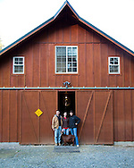 Amelia, Vern and Gianaclis Caldwell with one of the award winning Nigerian Dwarf Goats. (Deana) Standing outside the entrance to the goat barn.