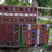 Asia, Bhutan, Bumthang. Textiles of Bhutan hanging outside shop.