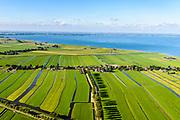 Nederland, Noord-Holland, Gemeente Edam-Volendam, 13-06-2017; Polder Zeevang met Zeevangse Zeedijk, IJsselmeerdijk ten noorden van Edam bij Warder. Hoorn aan de horizon.<br /> De dijk staat op de nominatie om verstrekt te worden, bewoners en actievoerders vrezen aantasting van de monumentale dijk en verlies culturele waarden.<br /> Zeevangse Zeedijk (seawall) north of Edam.<br /> The dike is nominated to be reinforced, residents and activists fear losing the monumental quality of the dike and losing other cultural values.<br /> <br /> luchtfoto (toeslag op standaard tarieven);<br /> aerial photo (additional fee required);<br /> copyright foto/photo Siebe Swart