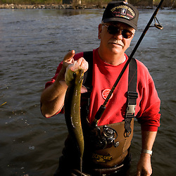 A fisherman lands a shad in the Connecticut River in Holyoke, Masschusetts.