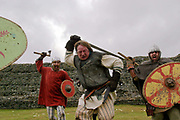Roman re-enactment society members recreate a battle scene at Richborough Roman Fort, Kent, UK