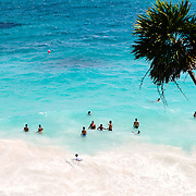 People swimming in the Caribbean Sea from one of the beautiful beaches next to the Maya civilizations ruins of Tulum on the eastern coast of Mexico's Yucatan Peninsula.