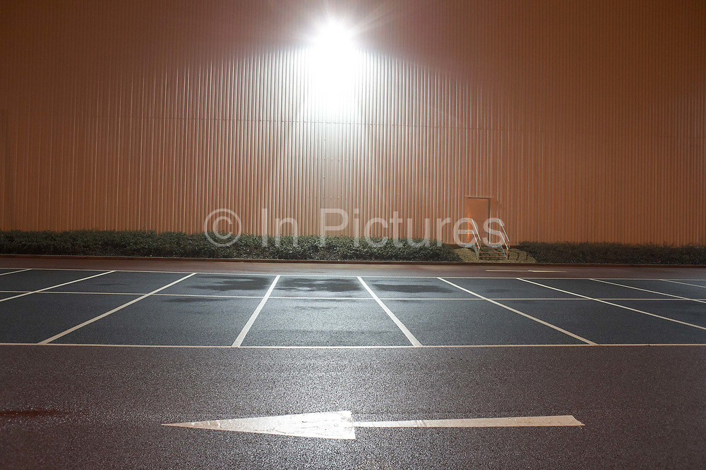 In front of empty parking bay markings, a stencilled arrow points from right to left in the foreground at the DIRFT warehouse logistics park in Daventry, Northamptonshire England. A bright light glows from the warehouse wall, shining  on to the car park creating an almost daylight landscape. This 365 acre site off Junction 18 of the M1 motorway is a hub for road, rail and service infrastructure, some 2.3m sq.ft. of distribution and manufacturing floorspace had been constructed by 2004 and occupiers including Tesco's, Tibbett & Britten plc, Ingram Micro, Royal Mail, the W.H. Malcolm Group, Eddie Stobart Ltd, Wincanton and Exel, have been attracted to this logistics location.