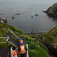 Tourists descend stairs below lighthouse at Cape Horn en route back to Chilean cruise ship, Mare Australis