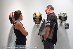Brian Klock and Vanessa Nay check out the helmet display at the Old Iron - Young Blood exhibition media and industry reception in the Motorcycles as Art gallery at the Buffalo Chip during the annual Sturgis Black Hills Motorcycle Rally. Sturgis, SD. USA. Sunday August 6, 2017. Photography ©2017 Michael Lichter.