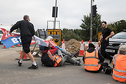 Enfield, UK. 15th September, 2021. An angry motorist removes a banner from Insulate Britain climate activists blocking a slip road from the M25 at Junction 25 as part of a campaign intended to push the UK government to make significant legislative change to start lowering emissions. The activists, who wrote to Prime Minister Boris Johnson on 13th August, are demanding that the government immediately promises both to fully fund and ensure the insulation of all social housing in Britain by 2025 and to produce within four months a legally binding national plan to fully fund and ensure the full low-energy and low-carbon whole-house retrofit, with no externalised costs, of all homes in Britain by 2030 as part of a just transition to full decarbonisation of all parts of society and the economy.