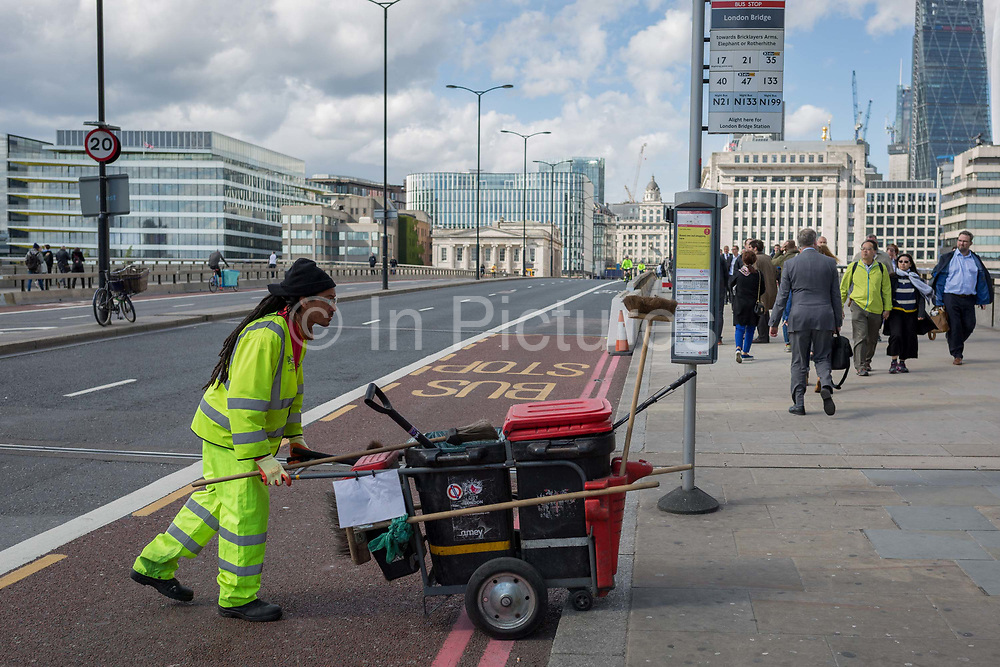 Three days after the terrorist attack in which 7 people died and many others suffered life-changing injuries on London Bridge and Borough Market, a contractor street cleaner crosses the still-closed road, on 6th June 2017, on London Bridge, in the south London borough of Southwark, England. City commuters now back at work walk respectfully and quietly past the floral memorial at the plinth marking the southern boundary of the City of London, the capitals financial district.