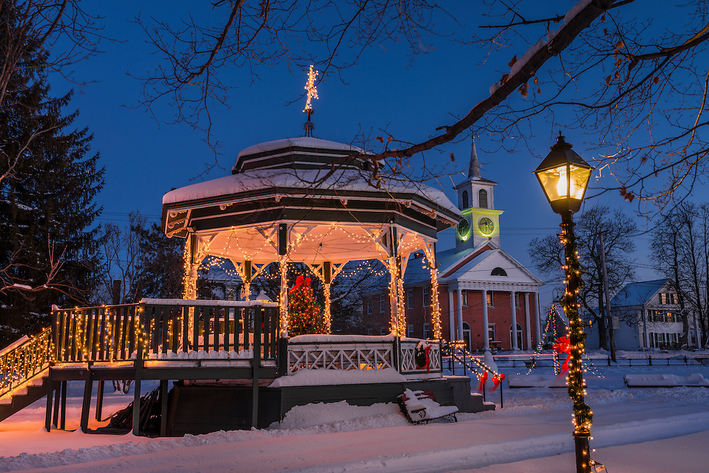 Winter scene of gazebo on town green with Christmas tree and lights at dusk, with benches and shoveled paths through snow, Townsend, MA