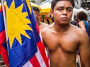 28 JULY 2013 - BANGKOK, THAILAND:  A Malaysian boxer carries his flag during the opening ceremonies the ASEAN Muay Thai Championship at MBK shopping center in Bangkok.      PHOTO BY JACK KURTZ