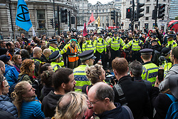 London, UK. 16 October, 2019. Police officers arrest climate activists from Extinction Rebellion who had defied the Metropolitan Police prohibition on Extinction Rebellion Autumn Uprising protests throughout London under Section 14 of the Public Order Act 1986 by sitting in the road in Whitehall.