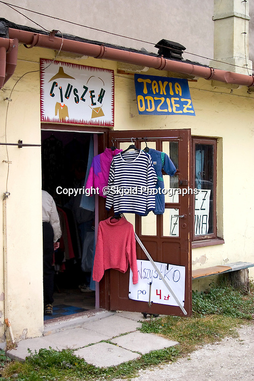 Clothing shop displaying goods hung on door outside.  Rawa Mazowiecka   Central Poland