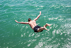 © Licensed to London News Pictures. 30/06/2019. Brighton, UK. Members of the public cool down by jumping in the sea in Brighton and Hove on one of the hottest days of the year so far. Photo credit: Hugo Michiels/LNP