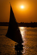 Luxor, Egypt. The sun sets over the Nile. A felucca on the East Bank.