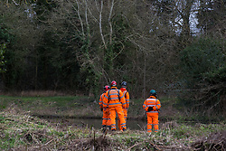 Denham, UK. 4 February, 2020. Engineers and security guards walk across land cleared for works for the HS2 high-speed rail link project in front of the river Colne. Planned works in the immediate vicinity are believed to include the felling of 200 trees and the construction of a roadway, Bailey bridge, compounds, fencing and a parking area. There is a wetland nature reserve adjacent to a Site of Metropolitan Importance for Nature Conservation (SMI) on the other side of the river.