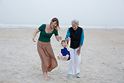 Grandmother and daughter swinging granddaughter on beach.