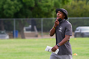 North Dallas Bulldogs football team Coach Andre Fuller, Receivers and Secondary Coordinator yells encouragement to his receivers during the first day of practice for the team since the onset of the Covid-19 Pandemic. <br /> (Photo by Jaime R. Carrero)