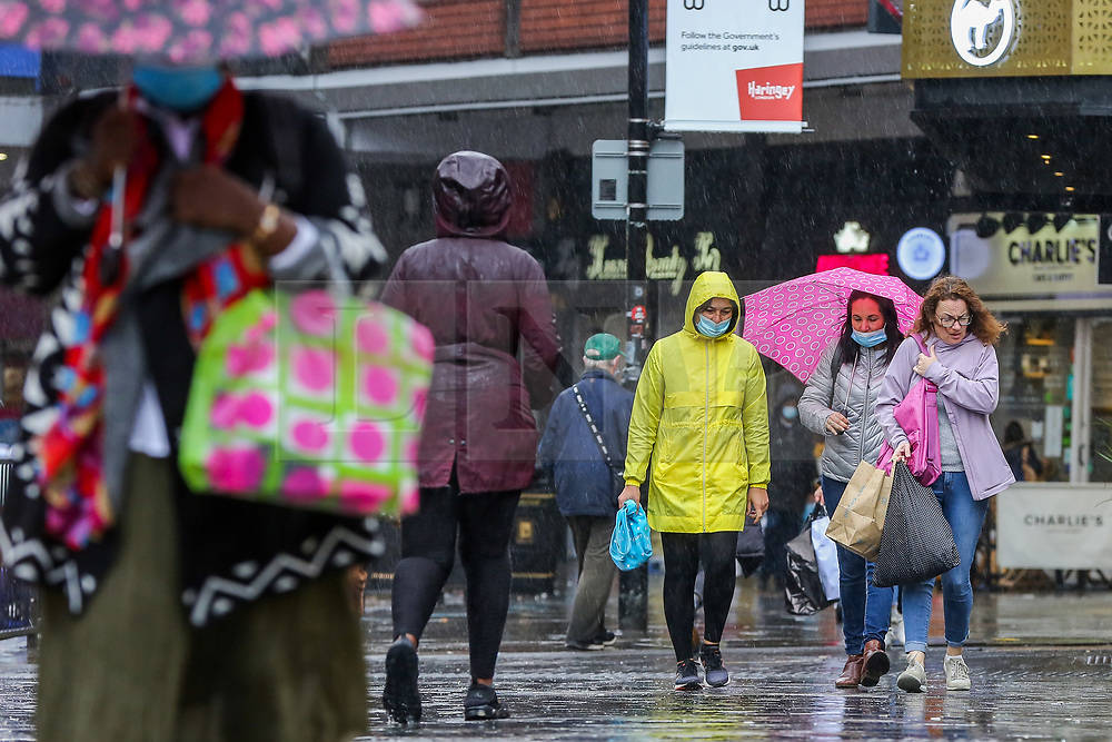 © Licensed to London News Pictures. 02/10/2020. London, UK. Members of the public wearing face coverings shelter from rain underneath umbrellas in north London as Storm Alex arrives from Europe. The Met Office forecasts heavy rain and windy weather for the next few days in the capital, caused by Storm Alex. Photo credit: Dinendra Haria/LNP