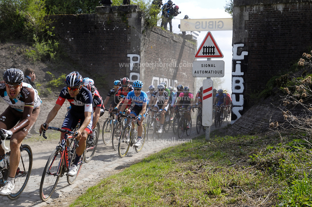France, April 13th 2014: The main group of riders pass through Pont Gibus, Wallers, in pursuit of the break during the 2014 edition of Paris Roubaix.