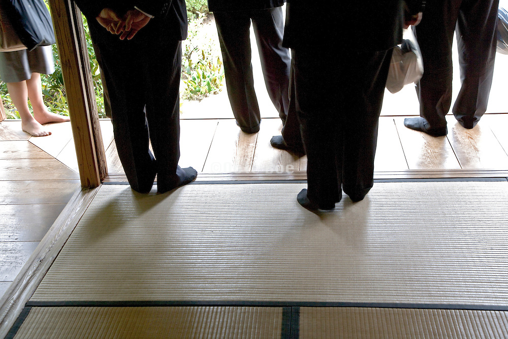 western businessmen shown around at a traditional Japanese garden and tea house