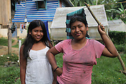 Madelin Montezuma (right) and her sister Lisbeth Montezuma, both Ngäbe women and members of COCABO, stand in front of a wooden home and a seed shelter used to dry cocoa beans. COCABO: Junquito, Almirante, Changuinola, Bocas del Toro, Panamá. September 1, 2012.