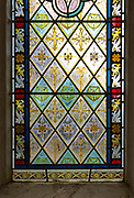 Nineteenth century decorative stained glass window floral geometric pattern flowers and crosses, Easton Royal, Wiltshire, England, UK