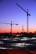 Cranes On The Job Site At Dusk