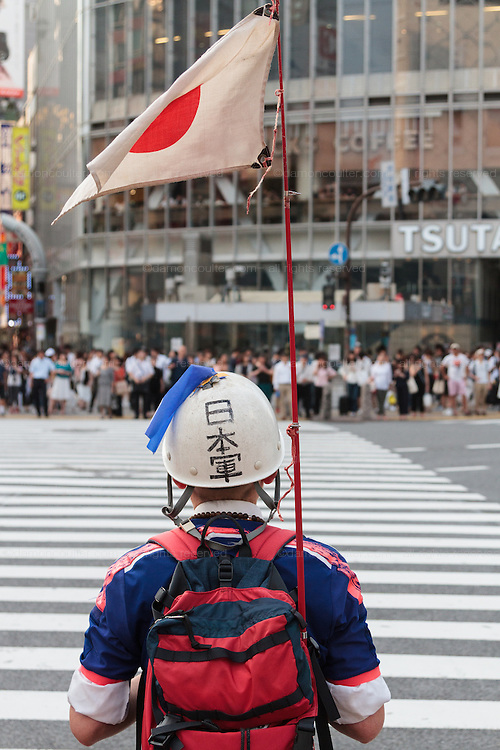 An old man dressed in Japanese soccer kits, wearing a helmet and carrying a Japanese flag waits to cross at Shibuya Crossing. Shibuya, Tokyo, Japan Friday June 17th 2016