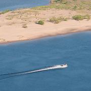 Motor boat in Volga river goes by a sand beach of Zelenenky island near Samara