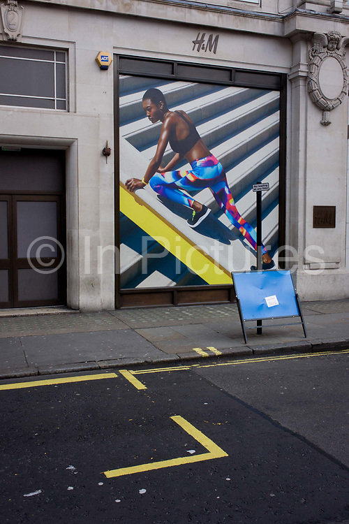 Stylish and athletic model on a billboard for clothing retailer H&M, in central London. We see a female adventurer wearing outdoor clothing, climbing up a diagonal slope on the billboard, the main colour being a yellow slant echoed by the lines painted on the ground, where London buses park before starting their routes. In 1947 Hennes women's clothing store opened in Västerås, Sweden. Today the H&M Group offers fashion for everyone under the brands of H&M, COS, Monki, Weekday, Cheap Monday and & Other Stories, as well as fashion for the home at H&M Home.