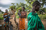 Elizabeth Ngobi, 35, center, stands while holding a neighbor's baby along with other Nuer survivors of sexual violence, Rebecca Agani, far left, and Nyabuol Tut, far right, in Bidibidi refugee settlement in Uganda. Elizabeth was raped by six Dinka soldiers in July 2015 in Juba and was shortly transferred to the UN compound. She had four children with her husband, but gave birth to a girl from the rape in early 2016 after she came to Uganda's Pagirinya refugee settlement. Her husband ran away from the fighting and she hasn't heard about him or her parents ever since.
