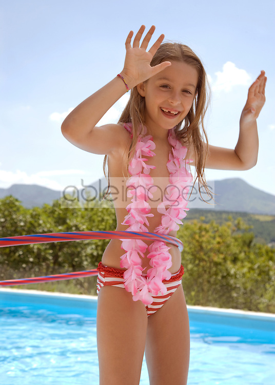 Young blonde girl with hula hoop and pink garland around neck by swimming pool