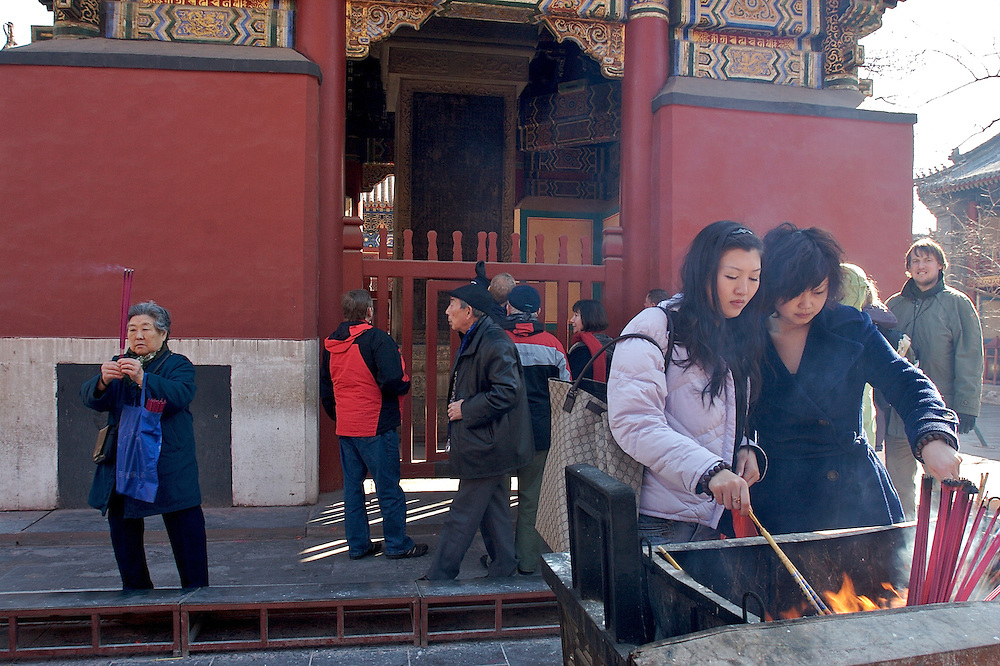 Two women light their incense sticks for prayer outside of a Yonghegong structure.  This Tibetan Temple is known to tourists as Lama Temple and it's located in Dongcheng District Beijing, China. This is the largest Temple of its kind outside of Tibet.  In 1723 the structure was turned into a Temple after the resident became the third Qing Emperor.