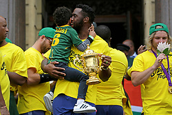 Monday 11th November 2019.<br /> City Hall, Grand Parade,<br /> And City Centre, Cape Town,<br /> Western Cape,<br /> South Africa.<br /> <br /> SPRINGBOKS CELEBRATE WINNING THE RUGBY WORLD CUP CHAMPIONSHIP IN 2019 WITH A COUNTRYWIDE VICTORY TOUR!<br /> <br /> SPRINGBOKS RUGBY WORLD CUP VICTORY TOUR CAPE TOWN!<br /> <br /> The Springboks take the stage outside the City Hall as they are cheered on by thousands of excited fans. South African Captain Siya Kolisi (centre) shares a moment with his son as he holds the Web Ellis Cup. Sniffing a Protea flower on the right is South African Scrumhalf Faf de Klerk.<br /> <br /> The reigning Rugby World Cup Champions namely the South African Springbok Rugby Team, celebrates winning the Webb Ellis Cup during the International Rugby Football Board Rugby World Cup Championship held in Japan in 2019 with their Victory Tour that culminated in the final city tour taking place in Cape Town. Thousands of South African fans filled the streets of the city all trying their best to show their support for their beloved Springboks and to celebrate them winning the Rugby World Cup for the third time. South Africa previously won the Rugby World Cup in 1995, 2007 and now again in 2019. South African Springbok Captan Siya Kolisi took the opportunity to speak to the gathered crowd about how something like this brings unity and that we should live together as a nation that practices what is known as ubuntu. Ubuntu is a quality that includes the essential human virtues of compassion and humanity. This image taken in Cape Town on Monday 11th November 2019.<br /> <br /> This image is the property of Seven Bang Media Group (Pty) Ltd, hereinafter referred to as SBM.<br /> <br /> Picture By: SBM / Mark Wessels. (11/11/2019).<br /> +27 (0)61 547 2729<br /> mark@sevenbang.com<br /> www.sevnbang.com<br /> <br /> Copyright © SBM. All Rights Reserved.