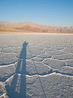 Photographer's shadow on salt pan at sunrise, Death Valley National Park, California