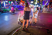 "21 JANUARY 2013 - BANGKOK, THAILAND:  A sex worker buys a snack from a street vendor in front of the Nana Entertainment Plaza, a red light district in Bangkok. Prostitution in Thailand is technically illegal, although in practice it is tolerated and partly regulated. Prostitution is practiced openly throughout the country. The number of prostitutes is difficult to determine, estimates vary widely. Since the Vietnam War, Thailand has gained international notoriety among travelers from many countries as a sex tourism destination. One estimate published in 2003 placed the trade at US$ 4.3 billion per year or about three percent of the Thai economy. It has been suggested that at least 10% of tourist dollars may be spent on the sex trade. According to a 2001 report by the World Health Organisation: ""There are between 150,000 and 200,000 sex workers (in Thailand).""  PHOTO BY JACK KURTZ"