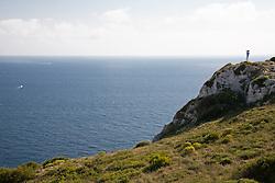Uomo che sullo stertto d'Otranto scruta l'orizzonte con un binocolo