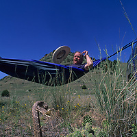Rob Hart, founder of Crazy Creek Products in Red Lodge, Montana, hams it up for a product photo of one of his hammocks (with a stuffed rattlesnake).