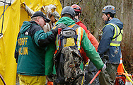 A sheriff's department chaplain (L) comforts a rescue worker heading into the decontamination tent after searching for victims at the mudslide in Oso, Washington March 30, 2014. Local churches offered prayers on Sunday for the victims of last week's devastating mudslide in Washington state and words of solace for grieving families and friends, many of whom are still waiting for news of missing loved ones.  REUTERS/Rick Wilking (UNITED STATES)