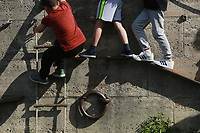 children playing climbing along a wall in a play area on the left back of the Seine River in Paris, France