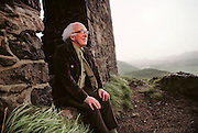 Physics: British theoretical physicist Professor Peter Higgs seen in Holyrood Park overlooking Edinburgh, Scotland (b. 1929). In 1964, Higgs predicted the existence of a new type of fundamental particle, commonly called the Higgs boson. This particle is required by many of the current Grand Unified Theories (or GUTs), which hope to explain three of the fundamental forces (electromagnetism, the weak & the strong nuclear forces) in a single unified theory. The Higgs boson is yet to be detected experimentally, but it is one of the main challenges of high-energy particle accelerators now being built. Higgs is professor of theoretical physics at Edinburgh University. MODEL RELEASED [1988]